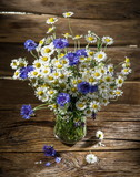 Bouquet of chamomiles and cornflowers in the vase on the wooden