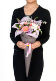 woman holds bouquet of crocus and gerbera. Valentine's Day