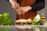 Chef cooks vegetables using salt-shaker. Collection of green vegetables on a whute surface