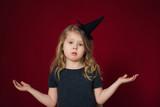 смешная девочка в волшебной шапке разводит руками