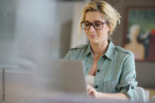 canvas print picture Portrait of blond woman working from home on laptop computer