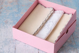 Gift for a holiday. Set handkerchiefs in a pink cardboard box on a light wooden background.