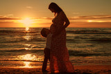 Pregnant woman with a boy on the beach at sunset