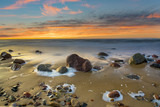 boulders on the sea beach at sunset