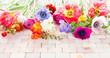 Leinwanddruck Bild - Bunte Fruehlingsblumen auf Stein