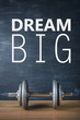 metal barbell on dark gray background and motivation text dream big