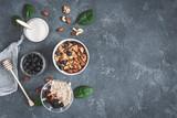 Healthy breakfast with muesli, yogurt, blueberry, nuts on grunge background. Flat lay, top view