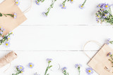 Flowers composition. Gifts and wildflowers on wooden white background. Flat lay, top view