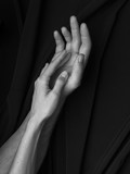 Black and white image, hands of man and woman tenderly touching each other on black background - 136962848