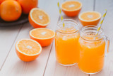 Fresh orange juice in a mason jar and orange sliced ripe on wooden table. Healthy eating concept.