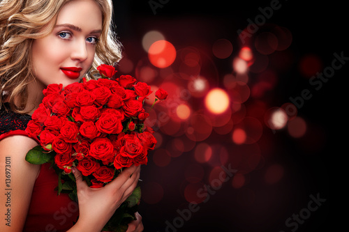 Beautiful blonde woman holding bouquet of red roses on bokeh background. Saint Valentine and International Women's Day, Eight March celebration. Copy space.
