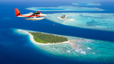 Sea plane flying above Maldives islands - 136984020