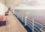 Cruise ship wooden promenade deck with beautiful runrays at sunset on the open sea.
