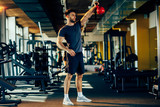 Handsome man lifting a kettlebell in the gym