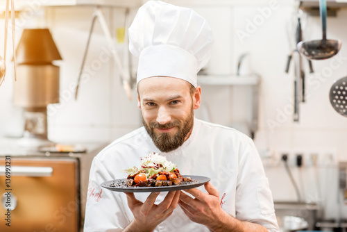 Portrait of chef cook in uniform standing with delicious dish at the kitchen