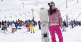 Pretty young asian woman on ski slope with snowboard  people on ski slope in background