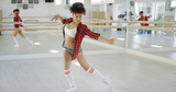 Female student extends both arms and one leg while performing dance moves in a studio