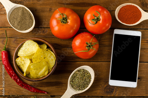 Poster Potato chips in a bowl on a wooden table, tomatoes and smartphon