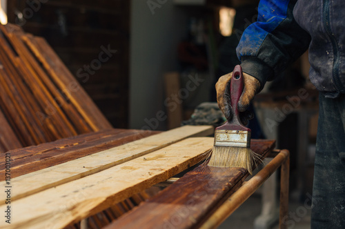 Varnishing a wooden plank using paintbrush - 137003021