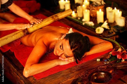 Bamboo massage of woman in spa salon. Girl on candles background in massage spa salon. Luxary interior in oriental therapy salon. Female have relax after sport.