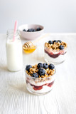 Cooking breakfast with granola and berries on white kitchen background