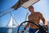 Skipper drives the sailing boat in the Aegean sea.