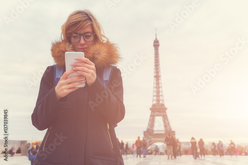 Using cellphone with Eiffel tower, Paris in the background. Photo by astrosystem