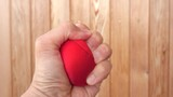 Hand squeeze red stress ball. Concept of anger, pressure and frustration.
