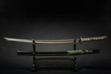 Japanese iaido sword in black wooden stand and black background. Still life studio shot with center light.