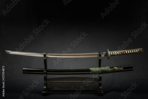 Japanese iaido sword in black wooden stand and black background Poster