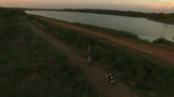 aerial view couples riding enduro motorcycle on dirt track