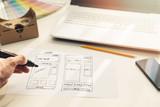 designer drawing website development wireframe on paper in office