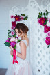 Classical beauty. Beautiful young woman with stylish brunette hair and elegant dress resting in luxury white classic room interior with folding screen and flowers. Spring portrait of elegant bride.
