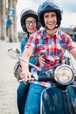 Junge Frau mit Helm auf dem Sozius Sitz eines Rollers in den Straßen von Berlin