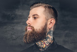 Bearded male with tattoo on his neck.