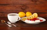 Кружка с черным чаем и тарелка с лимоном, сушеной вишней и зефиром на темном деревянном фоне.