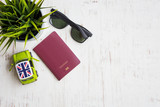 Passport, green car toy, artificial tree and sunglasses on white rustic wooden background, travel preparations concept