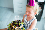 Cute little girl with her fruit birthday cake with two candles