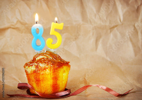 Poster Birthday cake with burning candles as number eighty five on brown paper backgrou