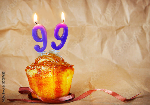 Birthday cake with burning candles as number ninety nine on brown paper backgrou Poster
