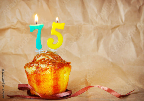 Birthday cake with burning candles as number seventy five on brown paper backgro Poster