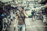 Muscular young handsome man walking on busy sunny street in Bangkok, Thailand.
