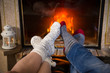 Legs in woolen socks stretched out heat up near fireplace
