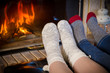 Legs in woolen socks stretched out to fireplace