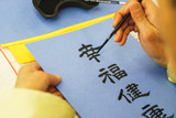 Elderly man painting brush and black ink Japanese characters on blue paper.
