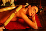 Bamboo massage of woman in spa salon. Girl on candles background in massage spa salon. Luxary interior in oriental therapy salon. Female have relax big stick after sport on red towel.