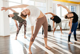 Group of people doing yoga stretching exercises in studio