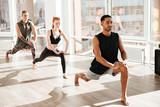 Group of barefoot people doing yoga exercises in studio