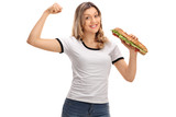 Happy woman flexing her biceps and holding a sandwich