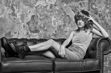 pretty girl in wig sitting on leather sofa, copy space